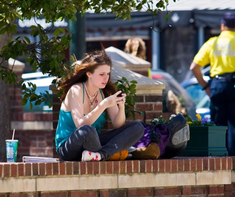 She could be accessing porn! In broad daylight! On her phone! And her parents would never even know!!! (Photo copyright Jeffrey Pott.)