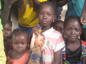 These little girls modified a second-hand blonde doll, giving her braids and traditional clothing.